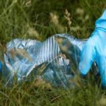 main gantée ramassant un déchet de bouteille plastique dans la nature